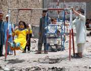 پشاور: بچے سڑک کنارے لگے جھولوں سے لطف اندوز ہو رہے ہیں۔