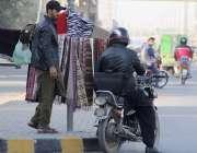 لاہور: فیروزپور روڈ پر ایک محنت کش گرم مفلر فروخت کررہا ہے۔