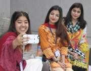 لاہور: جیل روڈ بس سٹاپ پر بیٹھی لڑکیاں سیلفی لے رہی ہیں۔