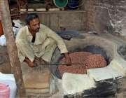 لاہور: محنت کش فروخت کے لیے مونگ پھلی بھون رہا ہے۔