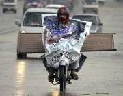 راولپنڈی: ایک موٹر سائیکل سوار نے بارش کے بچنے کے لیے پلاسٹک کی شیٹ ..