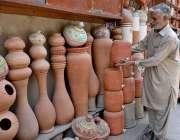 راولپنڈی: ایک معمر محنت کش گاہکوں کو متوجہ کرنے کے لیے مٹی کر برتن سجا ..