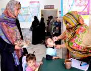 حیدر آباد: انسداد پولیو مہم کے دوران پولیو ورکر ایک بچے کو قطرے پلارہی ..
