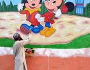 ملتان: پینٹر گورنمنٹ ایلیمنٹری کی دیوار پر کارٹون بنا رہا ہے۔