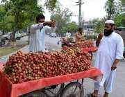 لاہور: ریڑھی بان لیچی کا تازہ رکھنے کے لیے پانی کا چھڑکاؤ کر رہا ہے۔