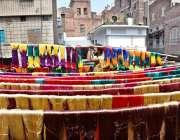 لاہور: رنگساز کپڑے خشک کرنے کے لیے دھوپ میں پھیلا رہا ہے۔