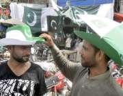 لاہور: اردو بازار میں ایک شخص قومی پرچم کے رنگوں والی ٹوپی خرید رہا ..