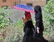 راولپنڈی: خواتین گرمی اور دوھوپ کی شدت سے بچنے کے لیے چھتری تانے جا ..