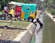 فیصل آباد: رکشہ ڈرائیور نہر کے پانی سے رکشہ دھو رہا ہے۔