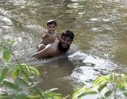 لاہور: ایک شہری گرمی کی شدت کم کرنے کے لیے اپنے بچے کے ہمراہ نہر میں ..