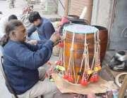 لاہور: ٹبی سٹی بازار میں ایک کاریگر ڈھول تیار کررہا ہے۔