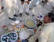 اسلام آباد: شہری فٹ پاتھ پر بیٹھے ایک شخص سے جڑی بوٹیوں سے تیار ادویات ..