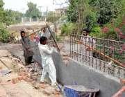 ملتان: مزدور گرین بیلٹ کی دیوار پر پر لولے کی باڑ لگانے میں مصروف ہیں۔