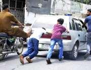 لاہور: بچے اور موٹر سائیکل سوار خراب گاڑی کو دھکا لگا رہے ہیں۔