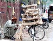 لاہور: لکڑی کی چوکیاں فروخت کرنے والا محنت کش سڑک کنارے بیٹھا کھانا ..