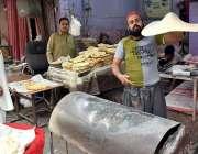 پشاور: فوارہ چوک فوڈ سٹریٹ میں ایک شخص روٹیاں پکا رہا ہے۔