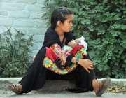 اسلام آباد: وفاقی دارالحکومت میں ایک بچے اپنی چھوٹی بہن کو گود میں لیے ..
