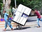 حیدر آباد: ایک معمر محنت کش ہتھ ریڑھی پر سامان لادھے جا رہا ہے جبکہ ایک ..