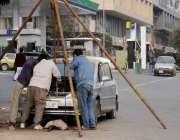 اسلام آباد: مکینک روڈ کنارے گاڑی کے انجن کی تیاری میں مصروف ہیں۔