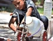 اسلام آباد: کمسن بچہ بوتل میں پینے کا پانی بھرنے کے بعد سائیکل پر رکھ ..