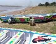 چنیوٹ: کارپینٹر کشتی بنانے کے بعد پینٹ کر رہے ہیں۔