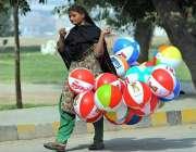 ملتان: خانہ بدوش خاتون پھیری لگا کر بیلون فروخت کررہی ہے۔