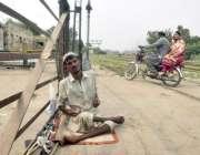 لاہور: ایک بھکاری ریلوے ٹریک کے قریب بیٹھا بھیک مانگ رہا ہے۔