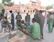 لاہور: ریلوے اسٹیشن کے باہر قلی کام نہ ہونے کے باعث درختوں کی چھاؤں ..