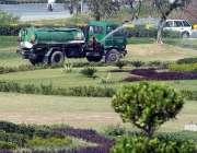 راولپنڈی: پی ایچ اے اہلکار گرین بیلٹ پر لگے پودوں اور گھاس پر پانی کا ..