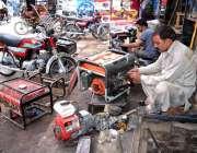 لاہور: مکینک اپنے ورکشاپ میں جنریٹر مرمت کرنے میں مصروف ہیں۔