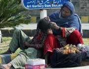 ملتان: خانہ بدوش خاتو ن اپنے بچوں کیہمراہ سڑک کنارے بیٹھی ہے۔