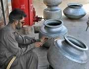 ملتان: مزدور دیگ کومرمت کرنے میں مصروف ہے۔