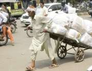 لاہور: ایک محنت کش ہتھ ریڑھی پر بھاری سامان رکھ کر لیجا رہا ہے۔