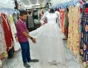 فیصل آباد: دکاندار گاہکوں کو متوجہ کرنے کے لیے کپڑے سجا رہا ہے۔