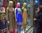 حیدر آباد: عید کی تیاریوں میں مصروف خاتون ایک دکان سے کپڑے پسند کر رہی ..