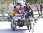 لاہور: خانہ بدوش اپنے بچوں کے ہمراہ گدھا ریڑھی پر پرانے کپڑے رکھے جار ..