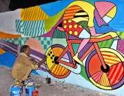 لاہور: ایک آرٹسٹ دیوار پر پینٹنگ کر رہا ہے۔