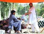 اسلام آباد: شہری سڑک کنارے لگے سٹال سے تربوز خرید رہا ہے۔