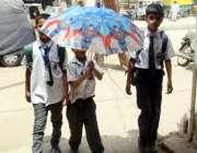 کراچی: سکول سے چھٹی کے بعد بچے چھتری تانے گھروں کو جا رہے ہیں۔