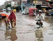 فیصل آباد: موٹر سائیکل سوار بارش کے بعد جمع ہونیوالے پانی سے گزر رہا ..
