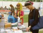 کراچی: تیسری سالانہ کتاب میلہ کے موقع پر طالبات ایک سٹال سے کتابیں پسند ..