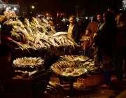 راولپنڈی: شہری سڑک کنارے لگے سٹال سے مچھلی خرید رہے ہیں۔