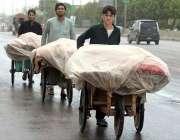 راولپنڈی: ریڑھی بان بارش سے بچائے کے لیے سبزی اور فروٹ پلاسٹک شیٹ کے ..