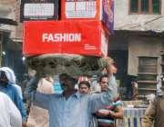لاہور: ایک محنت کش اپنے سر پر بھاری سامان اٹھا کر لیجا رہا ہے۔