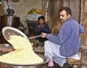 """لاہور: دکاندار ڈرائی فروٹ """"کاجو"""" روسٹ کررہا ہے۔"""