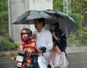 اسلام آباد: وفاقی دارالحکومت میں موٹر سائیکل سوار فیملی بارش سے بچنے ..