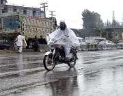 اسلام آباد: موٹر سائیکل سوار شخص نے بارش سے بچنے کے لیے پلاسٹ کے شیٹ ..