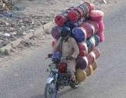 اسلام آباد: محنت کش موٹر سائیکل سوار گھریلو سامان لادے منزل کو رواں ..