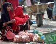 اسلام آباد: محنت کش خاتون سبزی منڈی میں پیاز فروخت کے لیے گاہکوں کی ..