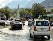 گلگت: موسلا دھار بارش کے بعد سڑک پر جمع پانی سے گاڑیاں گزر رہی ہے۔